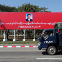 A police van drives by a banner welcoming Chinese President Xi Jinping ahead of his visit to Myanmar in Naypyitaw Thursday. | REUTERS