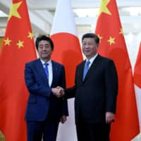Prime Minister Shinzo Abe shakes hands with Chinese leader Xi Jinping at the Great Hall of the People in Beijing on Dec. 23. | POOL / VIA REUTERS