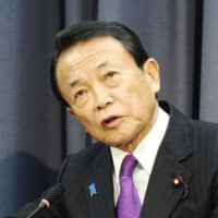 Finance Minister Taro Aso speaks at a news conference at the ministry in Tokyo on Tuesday. | KYODO