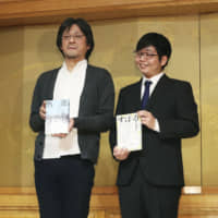 "Makoto Furukawa (right), winner of the Akutagawa Prize, and Soichi Kawagoe, winner of the Naoki Prize, hold copies of their respective books at a Tokyo hotel on Wednesday. | ‹?""¯"