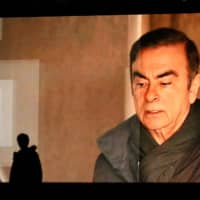 Pedestrians walk past a big TV monitor in Tokyo in April as Carlos Ghosn's image appears on a news program. Ghosn's stunning escape from Japan is bound to have an impact on future foreign suspects who seek to post bail, experts say. | PHOTOGRAPHER: TAKASHI AOYAMA/GETTY IMAGES