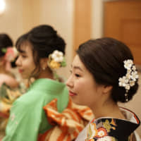 Ayana Fukushima (right) and her friends get ready for a coming-of-age ceremony at the Imperial Hotel in Tokyo on Monday. | RYUSEI TAKAHASHI