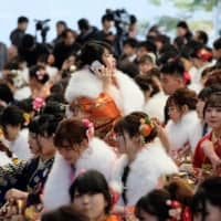Women draped in traditional kimono gather for their Coming-of-Age Day ceremony at Tokyo Disneyland in Urayasu, Chiba Prefecture, on Monday. | AFP-JIJI