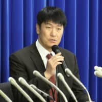 A health ministry official discusses the first case of a new coronavirus infection in Japan during a briefing at the ministry in Tokyo on Thursday. | KYODO