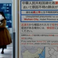 A woman wearing a mask walks past a quarantine notice about the outbreak of coronavirus in Wuhan, China at an arrival hall of Haneda Airport in Tokyo.