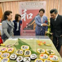 Yoshimasa Hayashi (second from right), then farm minister, looks at decorative sushi made to commemorate the registration of Japanese traditional food culture as an Intangible Cultural Heritage, at the farm ministry in December 2013.   KYODO
