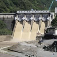 Kanogawa Dam in Ozu, Ehime Prefecture, conducted an emergency discharge of water during torrential rain that fell in the area in 2018. | KYODO