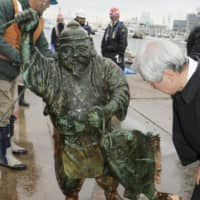 A statue of Ebisu, which was found underwater off Kesennuma port in Miyagi Prefecture, was pulled from the sea on Tuesday. | KYODO