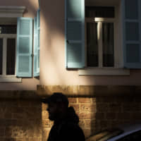 A private security guard stands outside the house of ex-Nissan chief Carlos Ghosn in Beirut on Monday.   AP