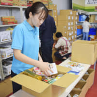 """A staff member at the nonprofit organization FoodBank Yamanashi packs foods in a box in Minami Alps, Yamanashi Prefecture, in September. 