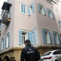 A private security guard stands outside the house of ex-Nissan chief Carlos Ghosn in Beirut Sunday. | AP