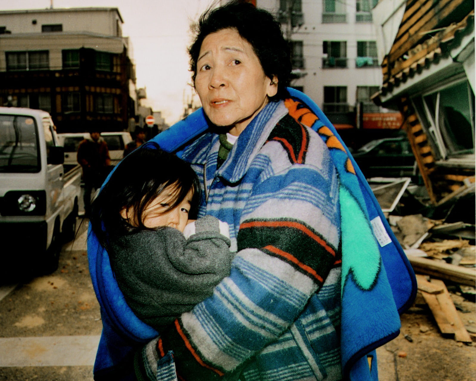 A woman in Kobe carries a child as she evacuates in the wake of the deadly Great Hanshin Earthquake on Jan. 17, 1995. | KYODO