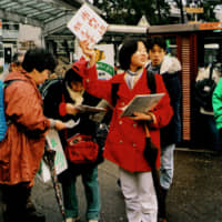 A high school volunteer hands out evacuation maps in front of a train station in Nishinomiya, Hyogo Prefecture, on Jan. 24, 1995. | KYODO