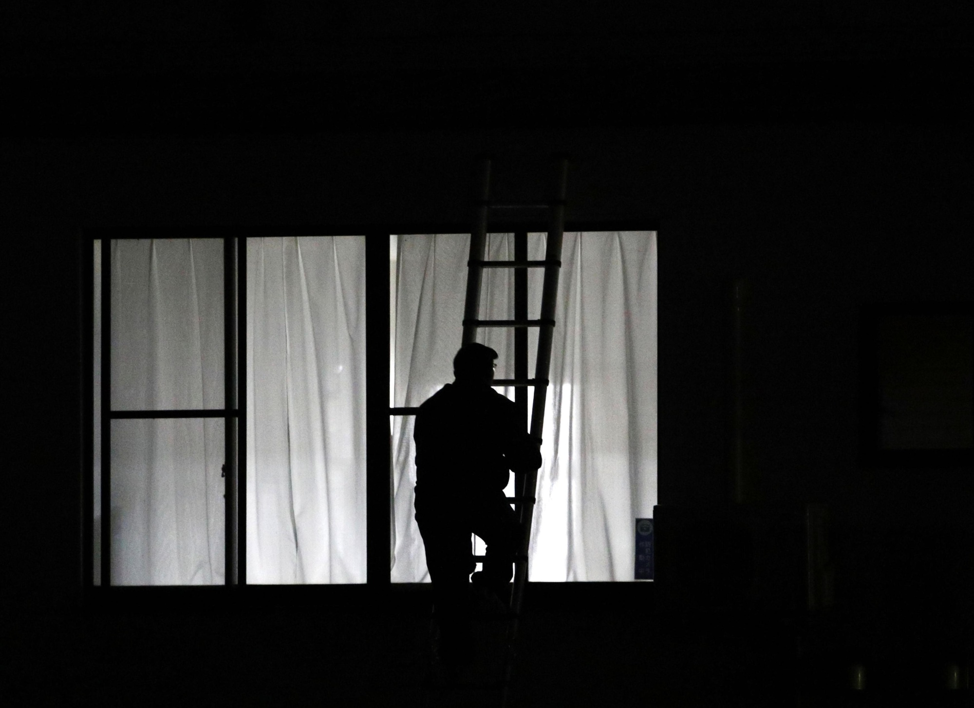 An investigator climbs a ladder early Wednesday morning outside the headquarters of Ueda Cold Corp. in Izumo, Shimane Prefecture, after a man barricaded himself in and took a female employee hostage.   KYODO