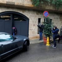 Journalists enter the garage of a house believed to belong to former Nissan Chairman Carlos Ghosn in Beirut on Thursday. | REUTERS