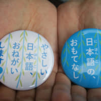 The city of Yanagawa, Fukuoka Prefecture, has made badges that can be worn by both tourists (left) and residents who prefer to speak in plain Japanese. | KYODO