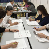 Participants study plain Japanese during a training session in Ashiya, Hyogo Prefecture, last October. | KYODO
