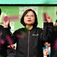 Taiwan President Tsai Ing-wen (center) celebrates with Vice President-elect William Lai (left) and Vice President Chen Chien-jen outside the campaign headquarters in Taipei on Saturday after her election victory. | AFP-JIJI