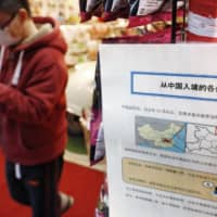 A sign displayed at a store in Osaka's Dotonbori shopping district on Thursday encourages people to go to the hospital if they have a fever. | KYODO