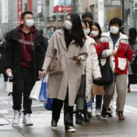 Chinese tourists wearing masks walk in Tokyo's Ginza district Sunday. | KYODO