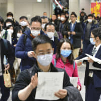 Passengers from China receive health questionnaires after arriving at Kansai International Airport in Osaka Prefecture on Friday at the start of the Lunar New Year holidays . | KYODO
