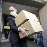 Investigators emerge from the office of former Justice Minister Katsuyuki Kawai on Wednesday. They are carrying boxes of materials seized during a raid at the location in the city of Hiroshima related to alleged election campaign violations by his wife during the Upper House election in July. | KYODO