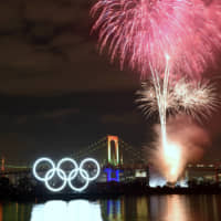 With the Olympic logo and Rainbow Bridge both lit up, fireworks explode over Tokyo Bay on Friday evening during an event to mark six months before the July 24 kickoff of the 2020 Games. | SATOKO KAWASAKI
