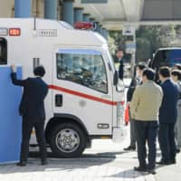 An ambulance carrying Japanese people who flew from Wuhan by a government-chartered plane arrives at a hospital in Tokyo's Ota Ward on Thursday. | KYODO