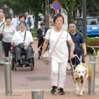 Members of a group for people with disabilities test out a route by foot between one of the 2020 Tokyo Olympic and Paralympic venues and its nearest station in Tokyo's Chofu in June 2017. | KYODO