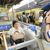 Aki Taguchi uses a wheelchair stair lift at JR Shinjuku Station in August 2018. The faces of other passengers in the background have been blurred for privacy reasons. | KYODO