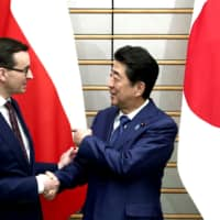Prime Minister Shinzo Abe welcomes Polish Prime Minister Mateusz Morawiecki on Tuesday, during a visit to Tokyo by Polish leader. | AFP-JIJI