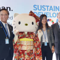 Kanagawa Gov. Yuji Kuroiwa (left) and Hello Kitty attend an event organized by the Japanese government to promote efforts to achieve the U.N. Sustainable Development Goals, at the U.N. headquarters in New York in July. | KYODO