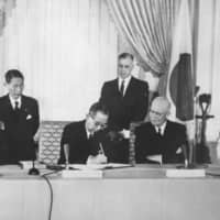 Then-Prime Minister Nobusuke Kishi (center left) signs the Japan-U.S. security treaty as U.S. President Dwight D. Eisenhower (center right) looks on at the White House in Washington in January 1960. | AP / VIA KYODO
