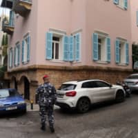 A Lebanese policeman patrols the street outside the property of Carlos Ghosn, former head of Nissan Motor Co. and Renault SA, in Beirut on Dec. 31. | BLOOMBERG