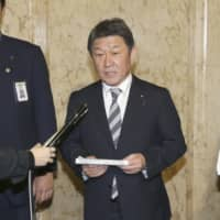 Foreign Minister Toshimitsu Motegi announces the dispatch of a chartered flight to Wuhan in Tokyo on Tuesday. | KYODO