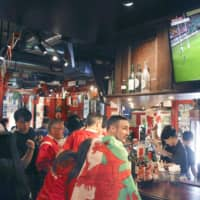 Tourists from overseas visit a bar in the city of Oita during the Rugby World Cup in October. | KYODO