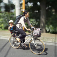 A woman takes her daughter to a day care facility in Tokyo. A recent government survey showed that a record 61 percent believe women should continue working after having a child. | KYODO