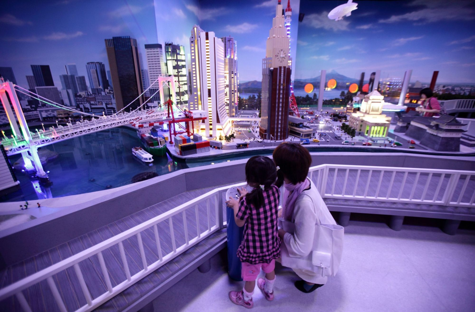 A child and her mother look at a diorama of Tokyo at night made by Lego A/S toy bricks at the Lego Land Discovery Center Tokyo in the capital in June 2012. A confluence of factors that include an aging population, falling birth rates and anachronistic gender dynamics are conspiring to damage women's prospects for a comfortable retirement. | BLOOMBERG