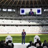 """Hello, proofreaders: Prime Minister Shinzo Abe speaks at the ribbon cutting for the new National Stadium in Tokyo. In the background, a sign reads """"Hello, Our Stadium."""""""