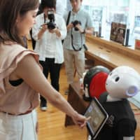 Bionic barista: A woman orders a coffee from Pepper the humanoid robot via a touch screen . | KYODO
