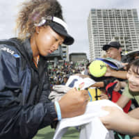 Modern role model: Tennis star Naomi Osaka signs autographs for fans in September last year. | KYODO