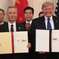 Chinese Vice Premier Liu He and U.S. President Donald Trump display their signatures on a bilateral trade agreement Wednesday. | AFP-JIJI