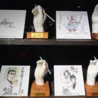 Handy exhibits: Plaster casts of manga and anime artists' hands are displayed with the artists' illustrations at the Kyoto International Manga Museum. | JASON JENKINS