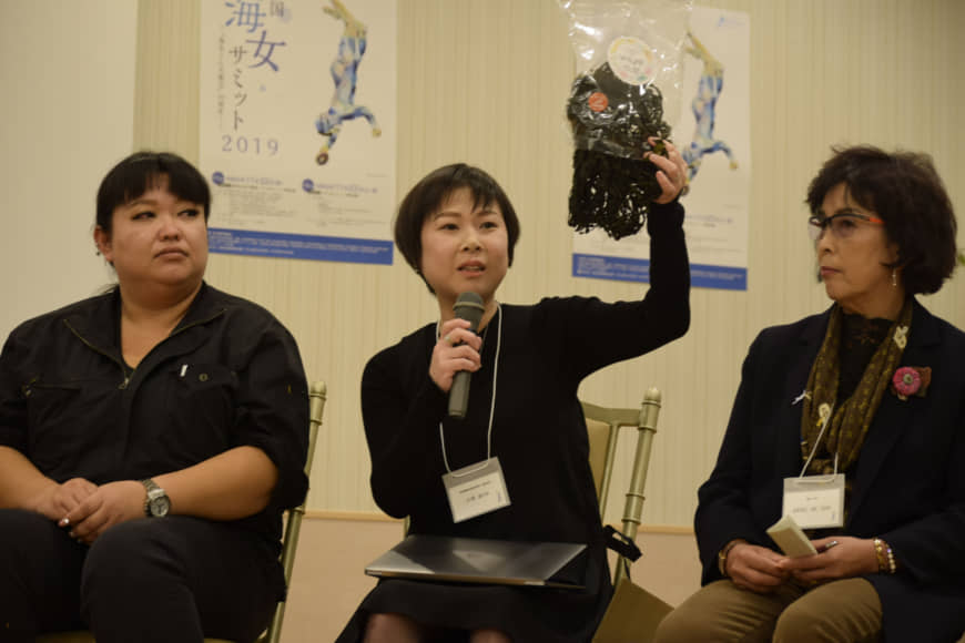New ideas: Megumi Kodera, an ama from the island of Sugashima holds up a seaweed product that she sells via online shopping apps, as she speaks during the 2019 November ama summit in Toba, Mie Prefecture. | KYODO
