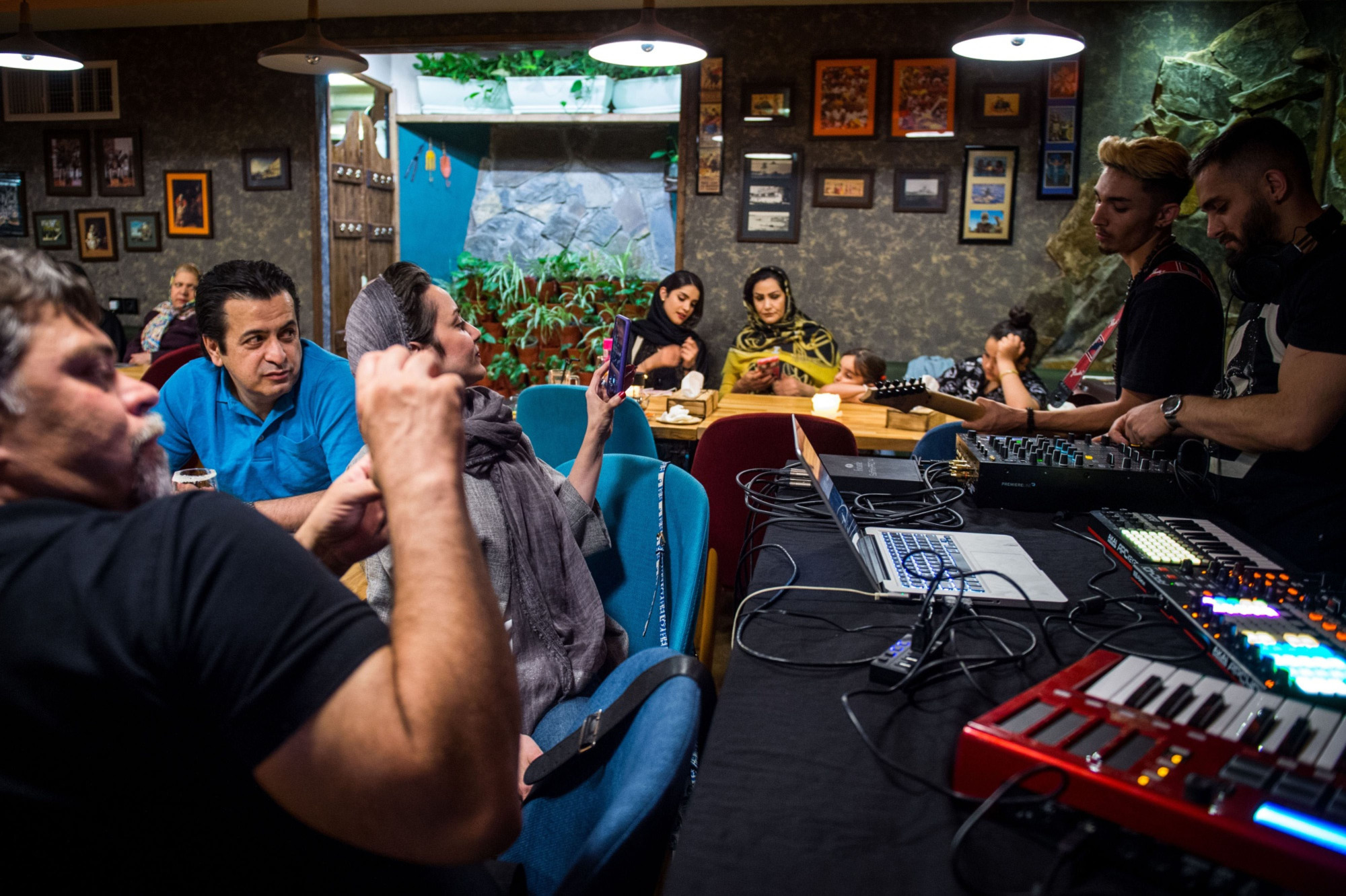 Iranians listen to live music at a night cafe in Tehran. In their lifestyles and aspirations, Iran's youth likely have more in common with their global peer group than any generation of Iranians since the 1979 revolution. | BLOOMBERG