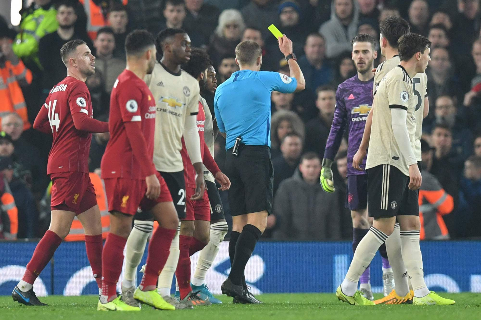 Referee Craig Pawson (center) books Manchester United goalkeeper David de Gea (third from right) for dissent during a Premier League match against Liverpool on Sunday at Anfield. | AFP-JIJI