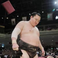 Hakuho returns to the locker room after losing his second straight bout of the New Year Grand Sumo Tournament on Tuesday at Ryogoku Kokugikan. The yokozuna withdrew on Wednesday with a 1-2 record. | KYODO