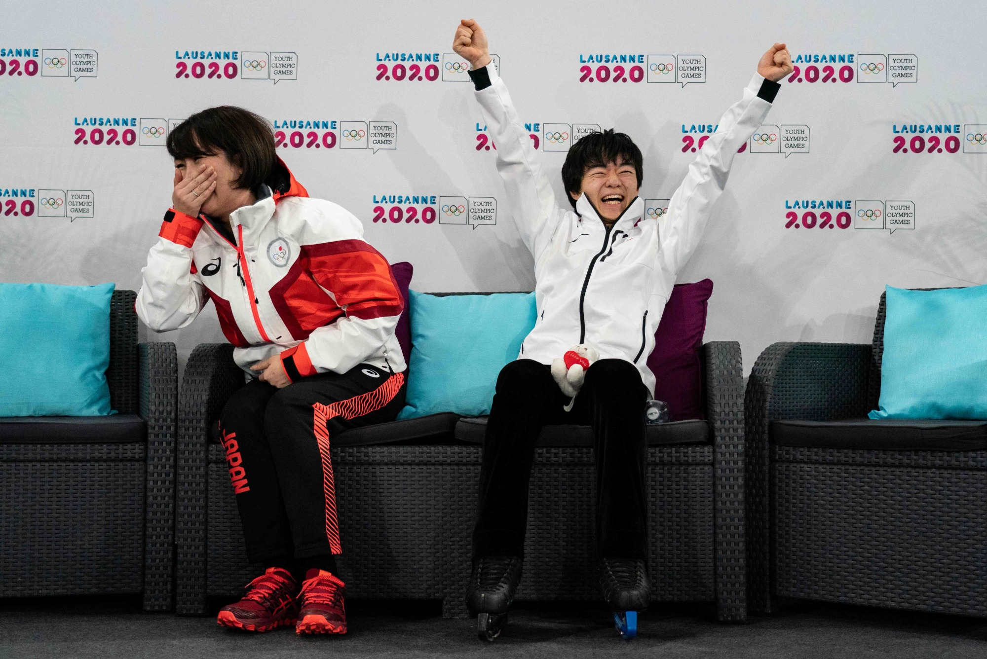 Yuma Kagiyama reacts alongside coach Misao Sato after winning the gold medal at the Winter Youth Olympics in Lausanne, Switzerland, on Sunday. | AFP-JIJI