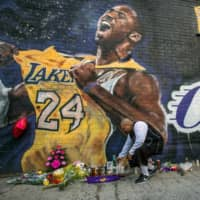 Luis Villanueva lights a candle in front of a Kobe Bryant mural in downtown Los Angeles on Sunday. | AFP-JIJI