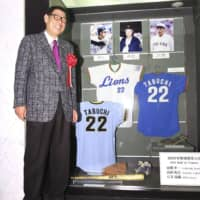 Koichi Tabuchi stands next to memorabilia from his playing days at the Japanese Baseball Hall of Fame Museum in Tokyo on Tuesday. Tabuchi was elected to the Japanese Baseball Hall of Fame on the same day. | KYODO